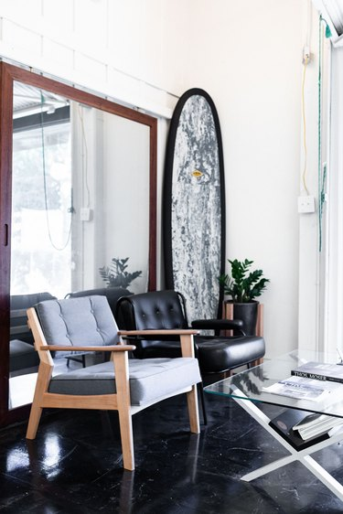 surfboard next to mirror and chairs in office space