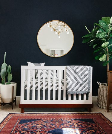 Navy blue nursery idea with white crib and round mirror hanging above with potted plants
