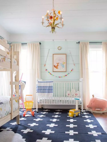 blue nursery idea with aqua shiplap walls and dark area rug