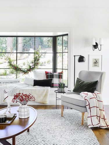 festive living room decorated for the holidays with a large wreath and plaid decor accents