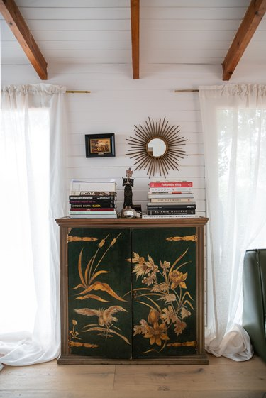 Green vintage, ornate dresser with books on top
