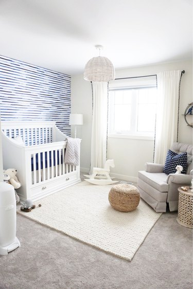blue nursery idea with white walls and furniture and carpet flooring with area rug