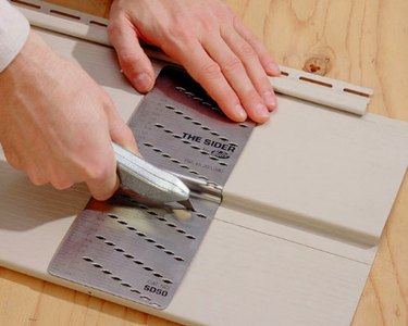 Cutting vinyl siding with a knife.