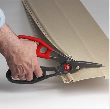 Cutting vinyl siding with tin snips.