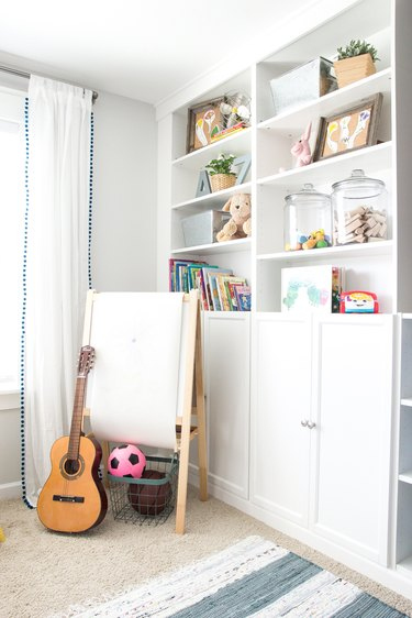 Built-in playroom storage idea with white shelving and drapery at window