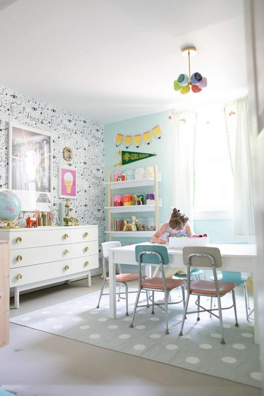 Vintage-inspired playroom storage idea with aqua walls and patterned wallpaper