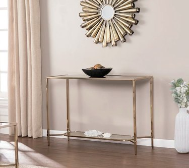 beige wall with art deco mirror and gold table