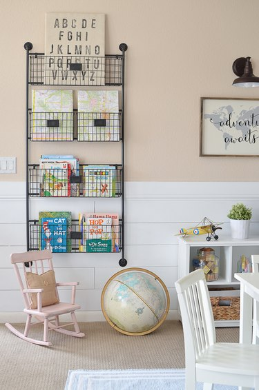 Vertical bookshelf playroom storage idea with blush walls and white furniture