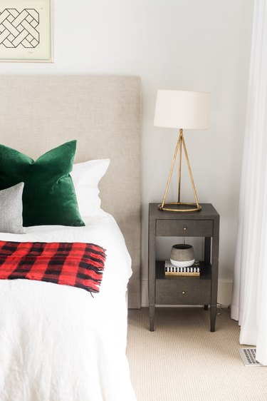 bedroom with red and black tartan throw and green velvet pillows