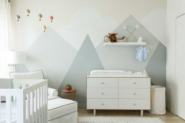 nursery idea for 2020 with blue geometric mural and white furniture