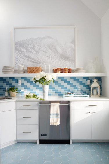 Kitchen with white cabinets and blue floor tile and backsplash