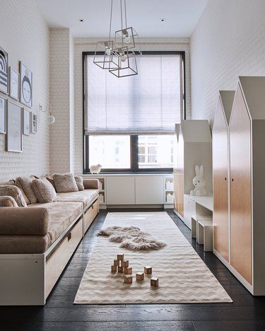 kids playroom idea with fun cabinets for storage and rug on wood flooring