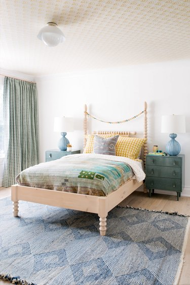 green kids bedroom idea with patterned ceiling and green nightstands