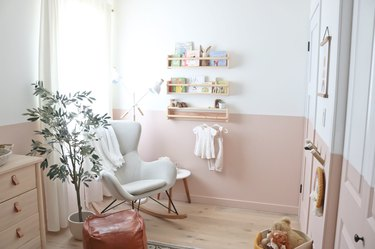 Pink and white baby nursery idea with color blocking and potted tree next to rocking chair
