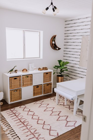 kids' playroom idea with storage and patterned wallpaper on wall