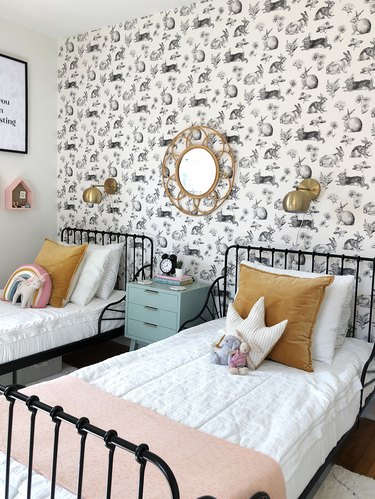kids' bedroom idea with patterned white wallpaper  and brass fixtures