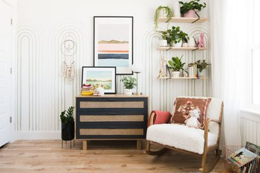 Vintage baby nursery idea with patterned wall paper and wall shelving with chest of drawers and rocker
