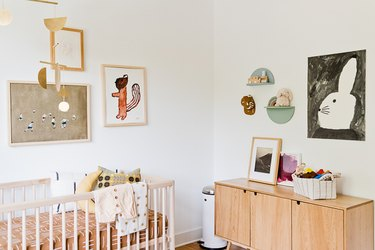 Artistic baby nursery idea with mobile hanging above crib and art on walls