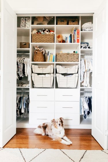 Closet nursery organization with drawers and shelving and rods for clothing