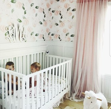 pink and white nursery idea with floral wallpaper and pink drapery