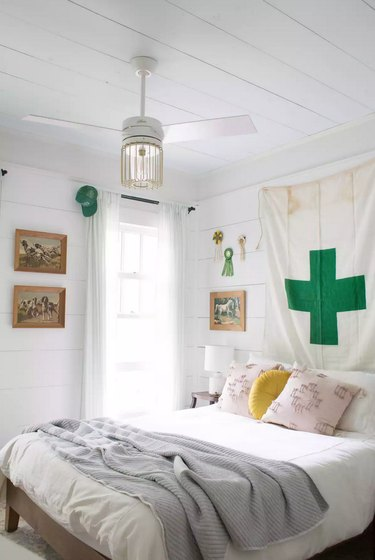 kids' bedroom idea with all-white palette and pops of green with tapestry on shiplap walls