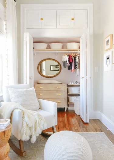 nursery organization in closet with changing table and mirror and shelving