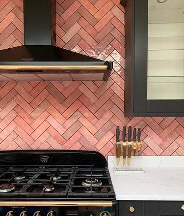 pink kitchen color idea with chevron backsplash and black cabinets