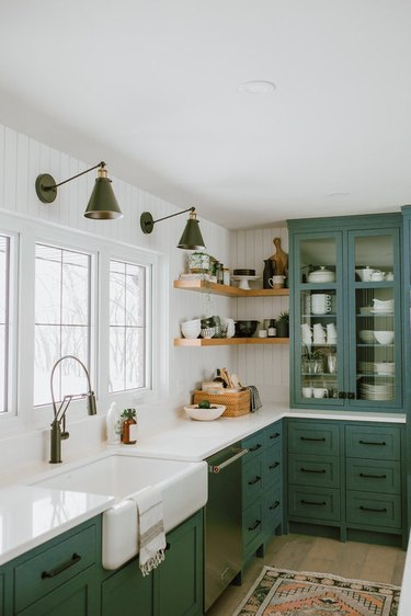 kitchen space with green cabinets and two light fixtures