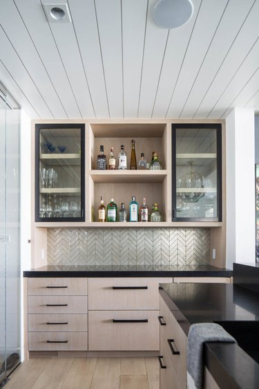 kitchen space with light wooden cabinets and glass kitchen cabinets