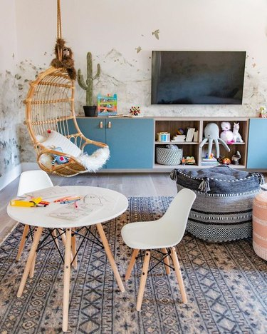 kids' playroom decor with patterned rug blue storage cabinet and wall mural