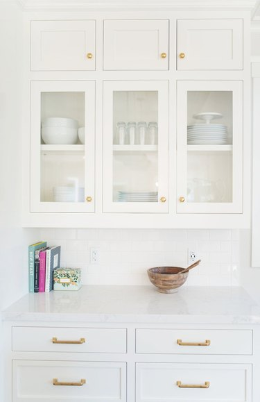 white kitchen cabinets with wood bowl and books on countertop
