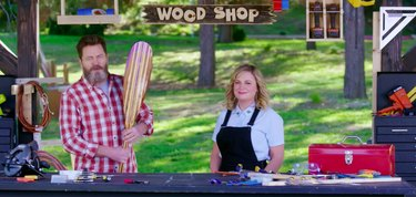 two people standing in a space with a sign that reads wood shop