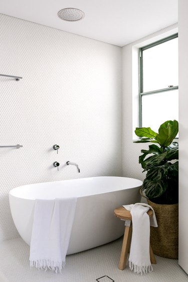 all-white bathroom with round penny tile mosaic on walls and floor