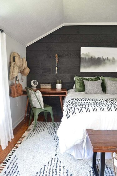 bohemian bedroom idea with thrift store decor and black shiplap wall