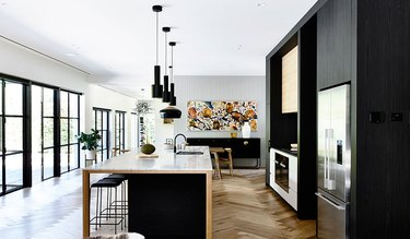 large open kitchen with black cabinets and stainless steel cabinets