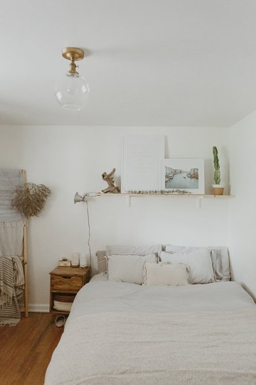 Vintage-inspired bohemian bedroom idea with white walls open shelving