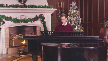 man sitting in front of piano in holiday decorated room