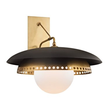 Black and brass sconce with white globe light and black outer shell over brass inner shell