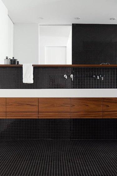 black bathroom with black mosaic floor and wall tile