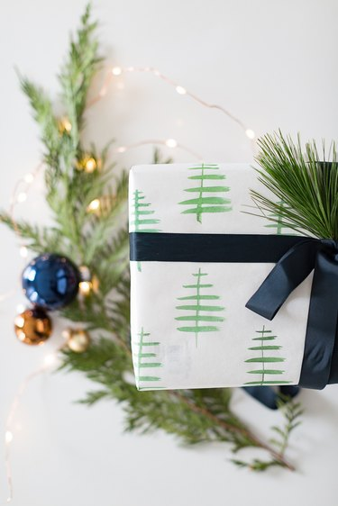 Beautifully wrapped present in white kraft paper with watercolor Christmas trees