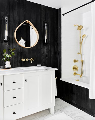 Black bathroom backsplash idea with stained wood walls, marble floor