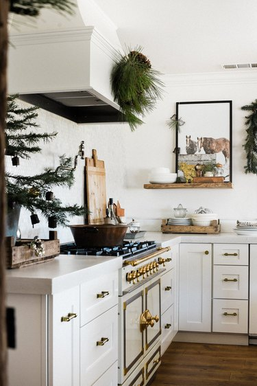farmhouse Christmas decorating idea in the kitchen with winter greenery and white accents