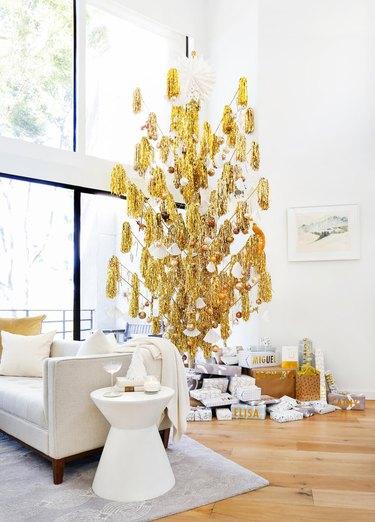 gold midcentury modern Christmas tree in white living room
