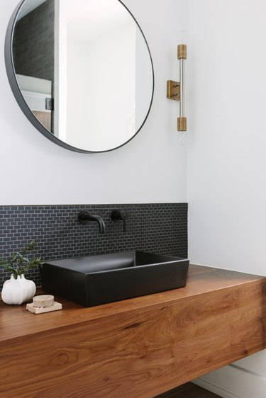 Black bathroom backsplash idea with vessel sink and matte hardware