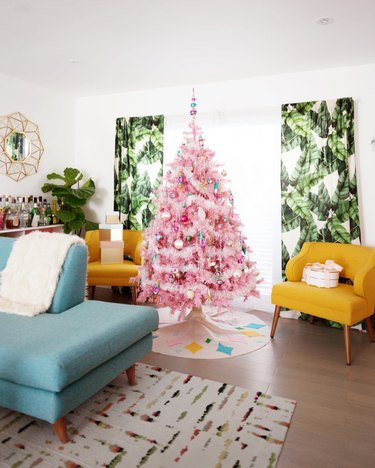 pink midcentury modern Christmas tree with ornaments next to window with tropical drapery