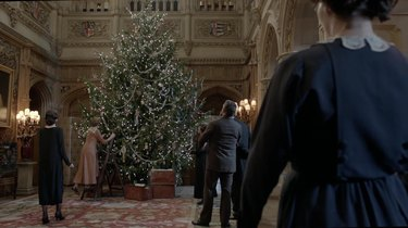 scene from Downton Abbey with figures around a Christmas tree