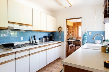 white kitchen with blue backsplash and tiled floor