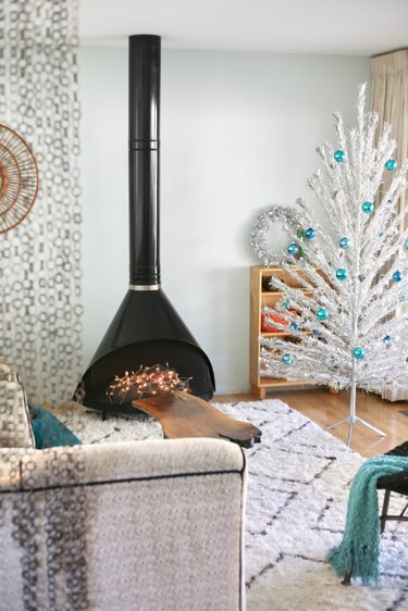white midcentury modern Christmas tree with turquoise blue ornaments and black midcentury fireplace
