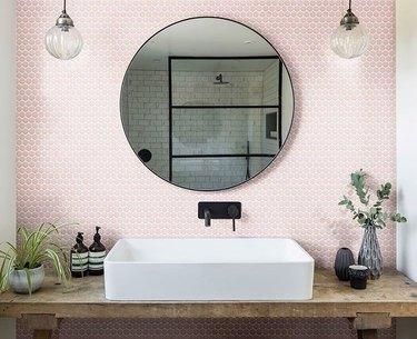 blush pink penny tile bathroom backsplash idea behind round mirror