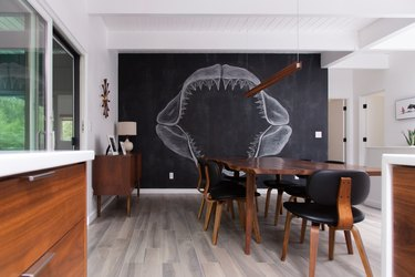 modern dining room with grey flooring and chalk wall